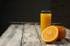 Corte de la fruta y zumo de naranja anaranjados en fondo de madera de la tabla, Foto de archivo libre de regalías
