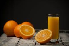 Corte de la fruta y zumo de naranja anaranjados en fondo de madera de la tabla, Imagen de archivo libre de regalías