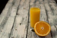 Corte de la fruta y zumo de naranja anaranjados en fondo de madera de la tabla, Imagenes de archivo