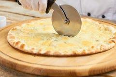 Corte de la pizza de queso por el cortador de la pizza de la rueda imagen de archivo libre de regalías