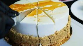 Corte de las manos del confitero del primer por la torta blanca de la crema batida del cuchillo metrajes