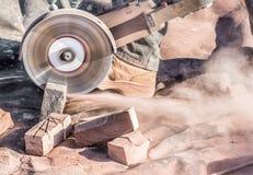 Corte de los ladrillos con la sierra circular imagen de archivo