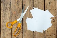 Corte de papel claro y tijeras en la tabla de madera Fotografía de archivo