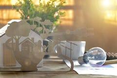 Corte de papel do eco na mesa Modelo da casa, lâmpada, pena, histórias do documento sobre as famílias de poupança de energia, fel imagens de stock