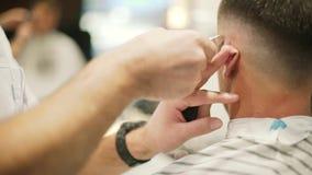 Corte de pelo masculino con la maquinilla de afeitar eléctrica Peluquero profesional que corta la máquina de afeitar eléctrica de almacen de metraje de vídeo