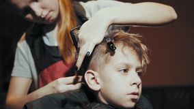 Corte de pelo para las tijeras y el peine del muchacho en el peluquero metrajes