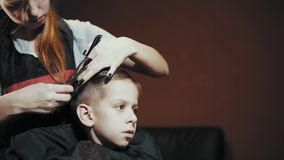 Corte de pelo para las tijeras y el peine del muchacho en el peluquero almacen de video