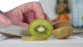 Corte del hombre con el cuchillo Kiwi Fruit en rebanadas verdes dulces y condimentadas frescas almacen de video