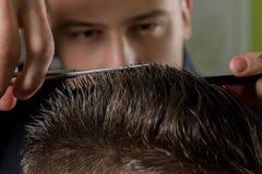 Corte del pelo de los hombres con las tijeras en un salón de belleza foto de archivo libre de regalías