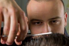 Corte del pelo de los hombres con las tijeras en un salón de belleza foto de archivo