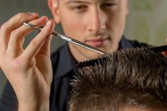 Corte del pelo de los hombres con las tijeras en un salón de belleza imagenes de archivo