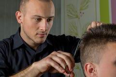 Corte del pelo de los hombres con las tijeras en un salón de belleza fotos de archivo