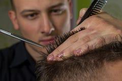 Corte del pelo de los hombres con las tijeras en un salón de belleza imagen de archivo