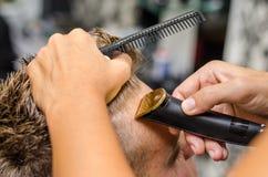 Corte del peluquero y pelo del modelado por el condensador de ajuste eléctrico Imágenes de archivo libres de regalías