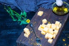 Corte del queso duro en pedazos cuadrados en un fondo marrón, cerca de un palillo transparente con la miel imagen de archivo
