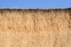Corte del suelo con diversas capas, hierba y el cielo Foto de archivo