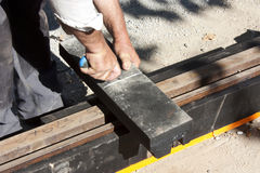 Corte del trabajador que humedece el material para las pistas de la tranvía Foto de archivo