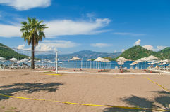 Corte di beach volley con i parasoli ed i lettini a fondo Fotografia Stock