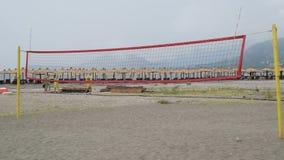 Corte di pallavolo sulla spiaggia, la gente che passa vicino archivi video