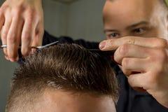 Corte do cabelo dos homens com tesouras em um salão de beleza foto de stock royalty free