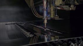 Corte do material de aço da chapa metálica lisa em um torno com o programa, tecnologia industrial moderna do laser do CNC brilhan filme