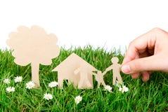 Corte do papel da preensão da mão da família sobre a grama verde. imagem de stock royalty free