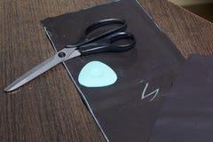 Corte do produto para costurar Na tabela é um pano com vestuários giz-marcados Apenas tesouras e giz da mentira fotografia de stock
