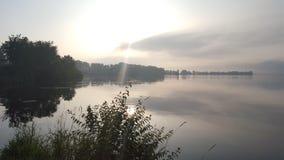Corte do raio de sol através do céu nublado no lago fotos de stock royalty free