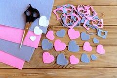 Corte dos corações do feltro, folhas ajustadas, sucatas sentidas de feltro, testes padrões de papel, tesouras no fundo de madeira Imagem de Stock Royalty Free