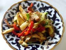 Corte dos vegetais às tiras e fritado preparado em um prato tradicional decorado de Usbequistão Fotos de Stock Royalty Free