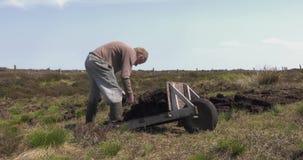Corte e turfa apropriada do relvado com uma pá no pântano do musgo na Irlanda filme