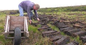 Corte e turfa apropriada do relvado com uma pá no pântano do musgo na Irlanda video estoque