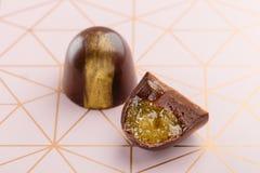 Corte el caramelo hecho a mano de lujo con el ganache del chocolate y el frui de la fruta cítrica Fotografía de archivo