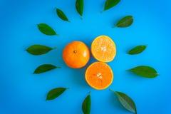 Corte el diseño de la fruta de naranja con la mesa en backgroun del azul de las placas Imagen de archivo