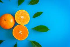 Corte el diseño de la fruta de naranja con la mesa en backgroun del azul de las placas Fotos de archivo