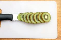 Corte el kiwi expuesto a los cuchillos Foto de archivo