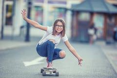 Corte el montar a caballo joven de la muchacha del patinador en su longboard en la ciudad Fotografía de archivo libre de regalías