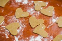 Corte el pan de jengibre en una forma del corazón en una tabla de madera, vertida con la harina de trigo fotografía de archivo