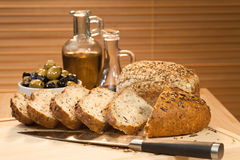 Corte el pan, el aceite de oliva y las aceitunas verdes y negras Foto de archivo libre de regalías