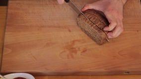 Corte el pan en una tabla de cortar almacen de metraje de vídeo