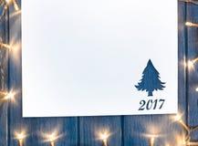 Corte el papel con las luces en forma del abeto en la tabla Imágenes de archivo libres de regalías