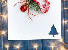 Corte el papel con las luces en forma del abeto en la tabla Foto de archivo libre de regalías