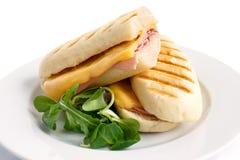 Corte el queso y el derretimiento tostado jamón del panini En la placa blanca con el garn Fotografía de archivo libre de regalías
