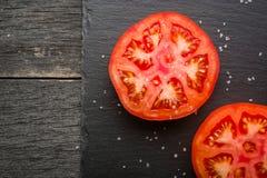 Corte el rojo del tomate con las semillas y los modelos Visión desde arriba Fondo de piedra negro de la pizarra Fotos de archivo