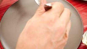 Corte el tomatoe y la seta asados a la parrilla con el cuchillo y la bifurcación inoxidables agudos Una placa redonda marrón con  almacen de metraje de vídeo