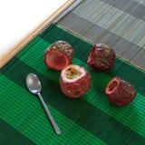 Corte el top de un passionfruit completo y tres frutas vacías con una cuchara en el lado en las esteras de bambú Fotografía de archivo
