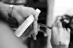 Corte en el peluquero del salón, primer del pelo de las tijeras en las manos del amo fotografía de archivo libre de regalías