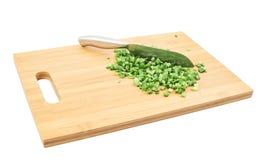 Corte en la cebolla verde de los pedazos sobre tabla de cortar Fotografía de archivo libre de regalías