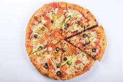Corte en pedazos de pizza con la carne, las aceitunas y las setas en un disco de madera Fotos de archivo