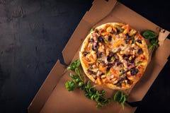 Corte en rebanadas deliciosas la pizza fresca con las setas y los salchichones en un fondo oscuro Visión superior Pizza en el neg fotos de archivo